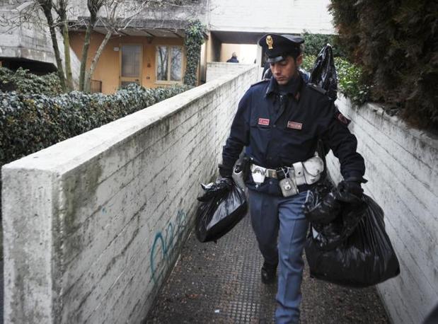 La polizia con alcuni oggetti sequestrati dal luogo dell'omicidio (Fotogramma Brescia)