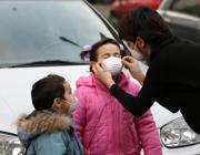 Una mamma mette mascherine antismog ai suoi figli (Fotogramma)